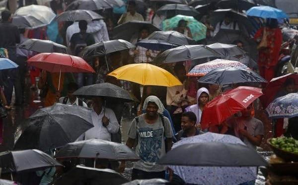 Pedestrians holding umbrellas walk through a market during monsoon rains in Mumbai