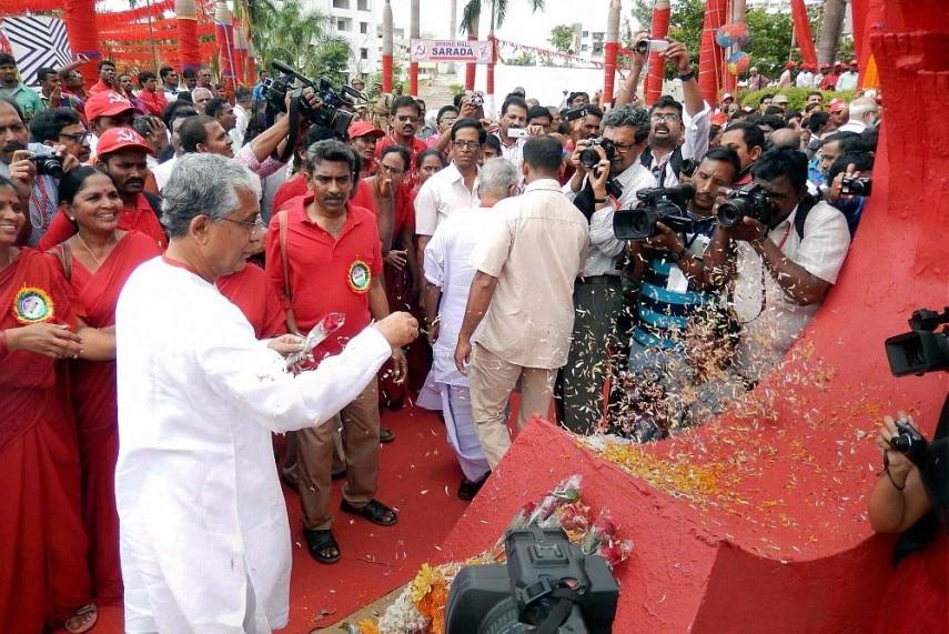 माणिक सरकार लेफ्ट के एक कार्यक्रम में केरल में. लाल झंडा लेकर चलते हैं, लेकिन कुर्ता हमेशा सफेद होता है. (फोटोःपीटीआई)