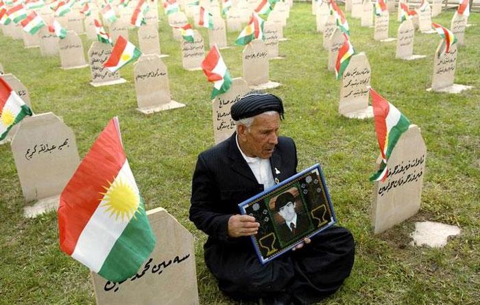 अपने बेटे की तस्वीर लेकर कब्रिस्तान में बैठे एक बुजुर्ग. इनका बेटा 16 मार्च, 1988 को हुए इसी केमिकल अटैक में मारा गया था.