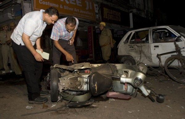Police and forensic experts examine a damaged scooter at the site of one of the bomb blasts in New Delhi September 13, 2008. At least five bombs exploded in quick succession in crowded markets and streets in New Delhi, killing at least 18 people and injuring scores more, police said. REUTERS/Stringer (INDIA) - GM1E49E08OF01