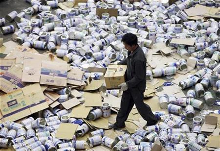 तस्वीर में एक अधिकारी द्वारा शंघाई में 14 नवंबर, 2008 को जब्त किए गए अयोग्य दूध पाउडर को नष्ट किया जा रहा है.