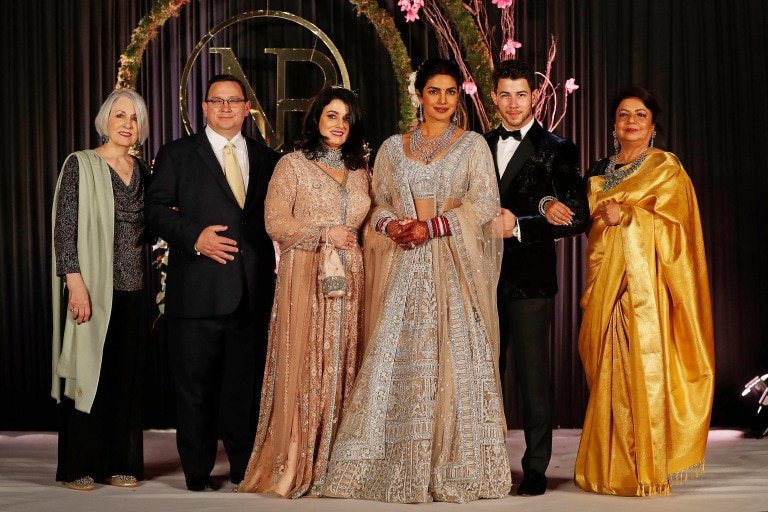 Mandatory Credit: Photo by Altaf Qadri/AP/REX/Shutterstock (10013599l) Priyanka Chopra, Nick Jonas. Bollywood actress Priyanka Chopra, third right and musician Nick Jonas, second right, stand for family photographs at their wedding reception in New Delhi, India Chopra Jonas Wedding, New Delhi, India - 04 Dec 2018