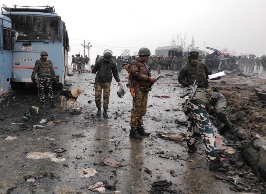 विस्फोट के बाद फैले मलबे को देखते सीआरपीएफ के जवान