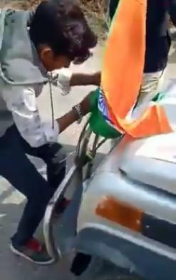 गाड़ी से तक़रीबन नोचकर तिरंगा झंडा उतारता शख्स वीडियो में दिखाई दे रहा है