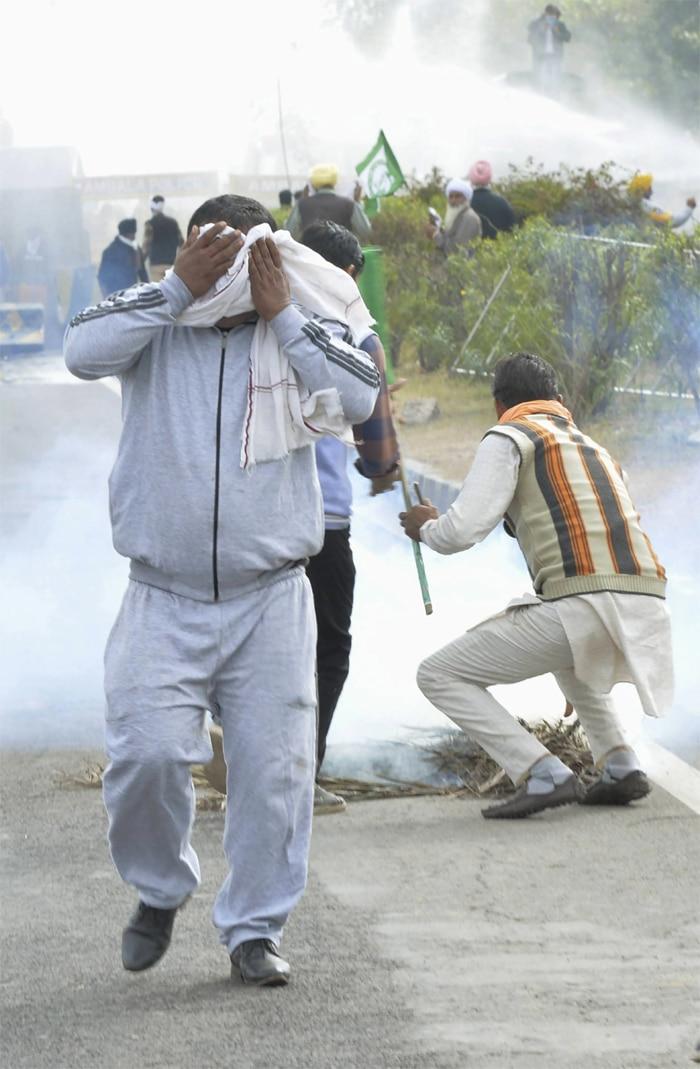 अंबाला के पास हरियाणा-पंजाब सीमा पर बने शंभू बोर्डर पर आंसू गैस से खुद को बचाता प्रदर्शनकारी. (तस्वीर-PTI, 26 नवंबर 2020)